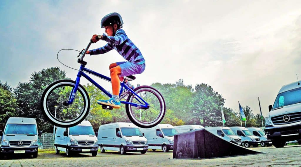 Young boy riding over a jump