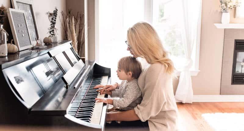 Mum teaching her child to play piano