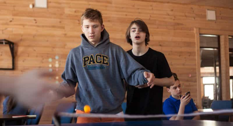 Young guys playing table tennis in game room