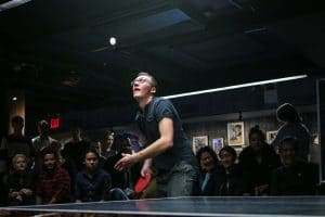 Ping pong player serving with crowd
