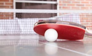 White ball under a red paddle rubber grip